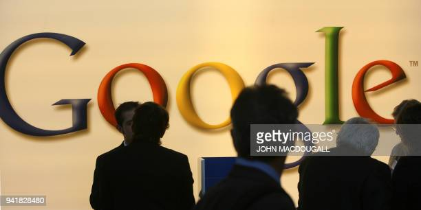 Fair-goers and German police officers walk past the US search engine giant Google's stand at the Frankfurt Book Fair 04 October 2006. Human rights...