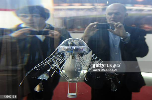Fairgoers take pictures of Festo's Aquajelly an artificial autonomous jellyfish with an electric drive and an intelligent adaptive mechanical system...