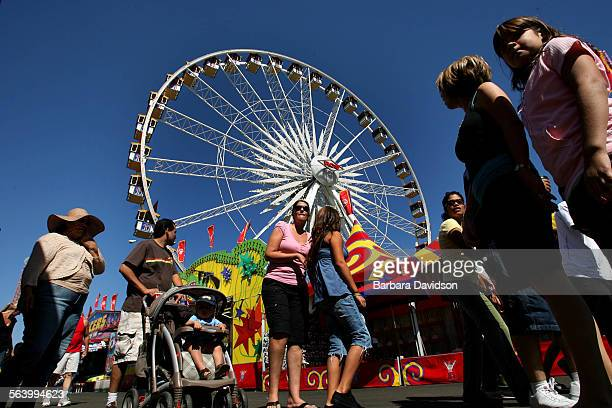 Fairgoers walk the grounds near the huge ferris wheel Sept 30 07 on last day of the LA County Fair in Pomona CA