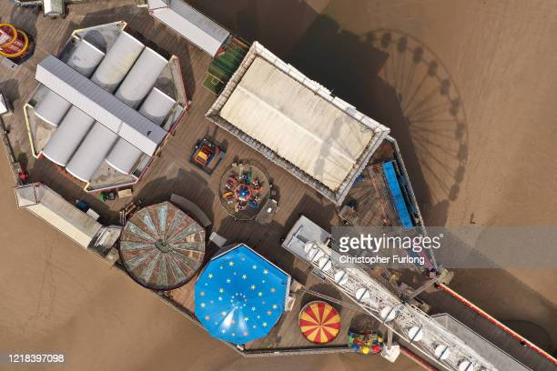 Fairground rides lay dormant and the beach and promenade deserted as people heed the official advice and stay home on Easter Sunday traditionally a...