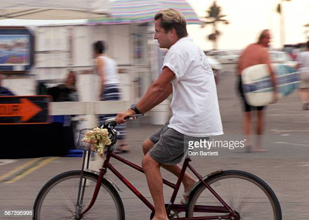 LSFairLabokDB090498––HuntingtonBeach –– Bruce Labok pedals along Walnut Ave on his old bike with a basket of tuber roses The local resident says he...