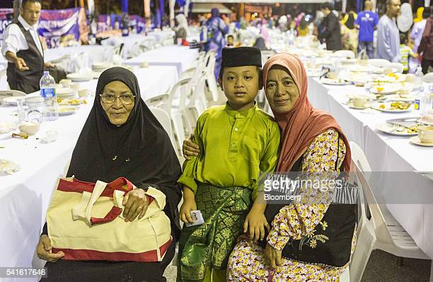 Fairuzita Mohamad Amir right sits with her son and mother for a photograph at a Barisan Nasional party election event at a mosque in Sungai Besar...