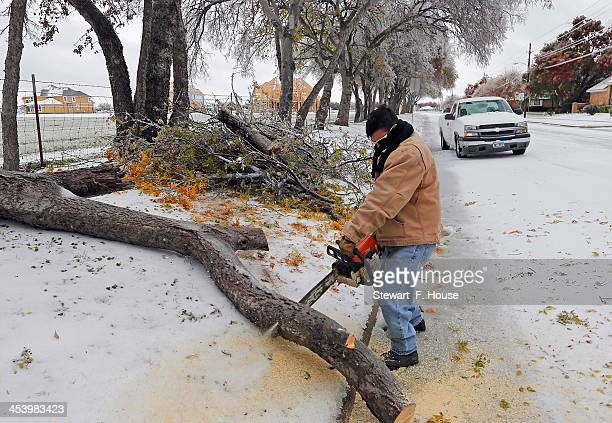 Fairview Farms employee Julio Rodriguez of Plano Texas uses a chain saw to remove downed tree trees and limbs from the residential streets near the...