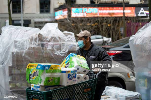 Fairway employee wheels a shopping cart full of paper products into the store to restock the shelves amid the coronavirus pandemic on April 24 2020...