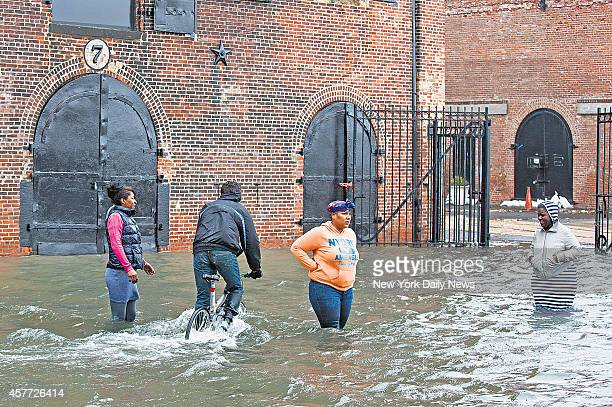 Fairway employees walk through the flood waters around the grocery store just to see how the building is holding up in Red Hook Brooklyn Monday...