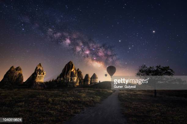 fairy chimneys with milky way and hot air ballons at cappadocia, goreme, turkey - milky way stock pictures, royalty-free photos & images