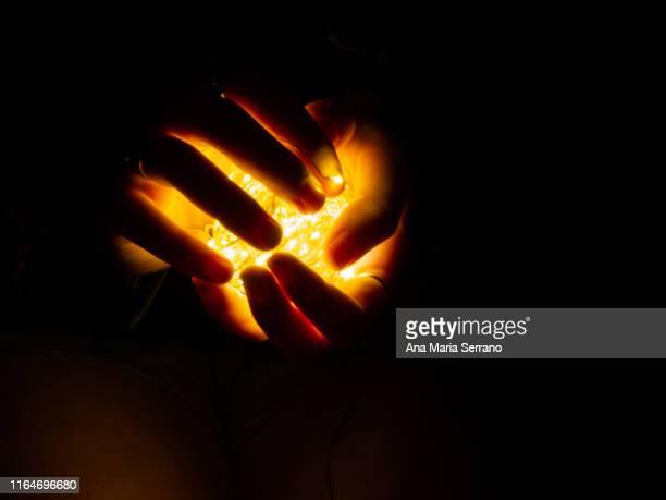 fairy lights illuminating a woman's hands - mago imagens e fotografias de stock