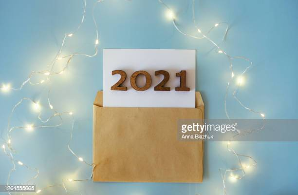 fairy silver lights with craft paper envelope and 2021 number of new year. festive new year's concept. blue winter background. - happy new month stock pictures, royalty-free photos & images