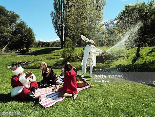 Fairy tale characters, Santa Claus and superhero having picnic