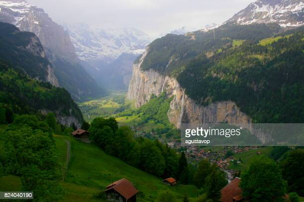 Fairy tale landscape: above idyllic Staubbach waterfall in Lauterbrunnen alpine village, cityscape valley and meadows, dramatic swiss snowcapped alps, idyllic countryside, Bernese Oberland,Swiss Alps, Switzerland