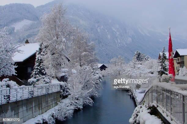 Paisaje de cuento de hadas: pueblo alpino de Interlaken bajo caída de la nieve, reflejo del río, paisaje cubierto de nieve blanca, espectacular Suiza Alpes nevados, paisaje idílico, Oberland bernés, Alpes suizos, Suiza