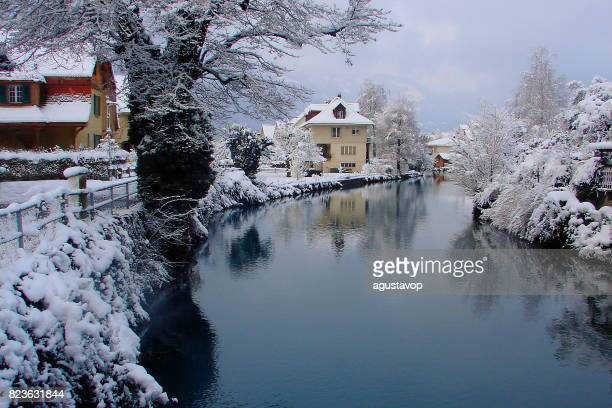 Fairy tale landscape: Interlaken alpine village under snow fall, river reflection, white Snowy cityscape, dramatic swiss snowcapped alps, idyllic countryside, Bernese Oberland,Swiss Alps, Switzerland