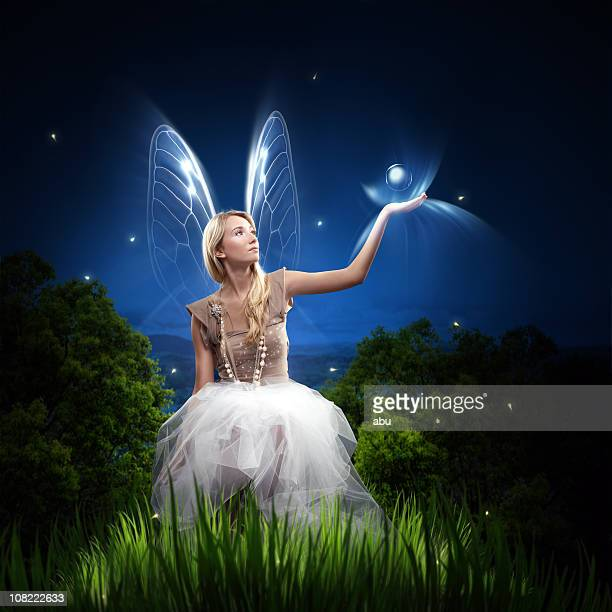 fairy woman holding orb and sitting in grass - fairy stock photos and pictures