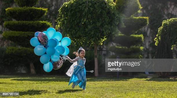 Fairytale girl outdoors in nature with balloon