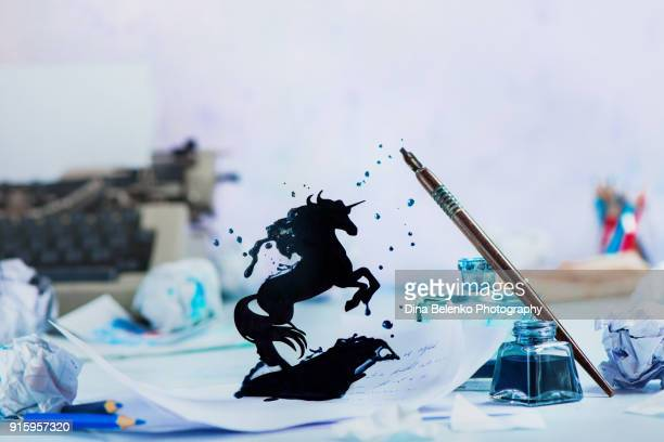 Fairytale writing prompt with unicorn silhouette made from splashes of ink from fountain pen and inkwell. Writer workplace with typewriter, pencils and papers on a light background with copy space. Creative writing concept with frozen motion.