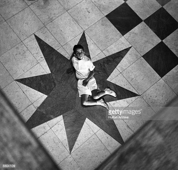 Faisal II king of Iraq from 1939 sits on a star decoration on the floor
