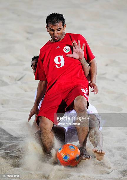 Faisal Mohammed Al Balushi of Oman is tackled from behind in the Men's Beach Soccer Quarterfinal match between Oman and Bahrain at AlMusannah Sports...
