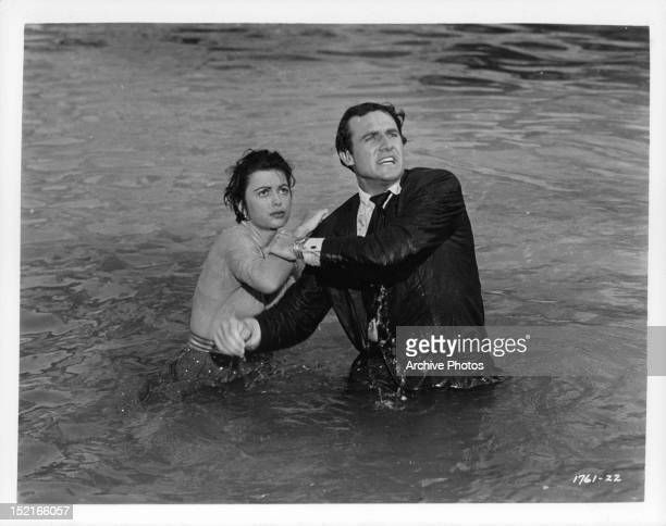 Faith Domergue and Rex Reason wading through the water together in a scene from for the film 'This Island Earth' 1955