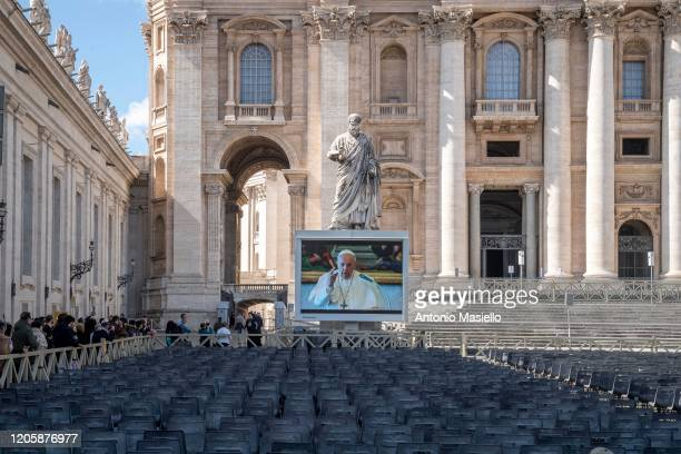 Faithful attend the live-broadcasting of Pope Francis' Sunday Angelus prayer during the Coronavirus emergency at Saint Peter's Square, on March 8,...