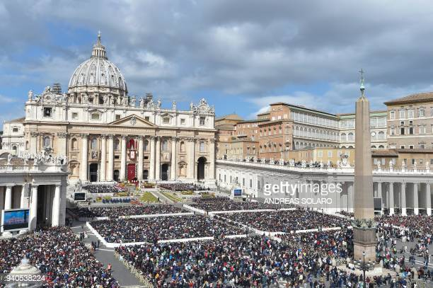 TOPSHOT Faithful attend the mass of Easter celebrated by Pope Francis on April 1 2018 at St Peter's square in Vatican Christians around the world are...