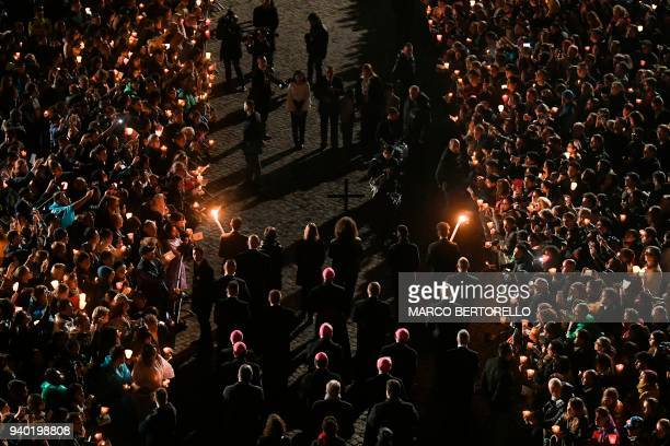 Faithful attend the Via Crucis torchlight procession at the Colosseum on Good Friday on March 30 2018 in Rome Christians around the world are marking...