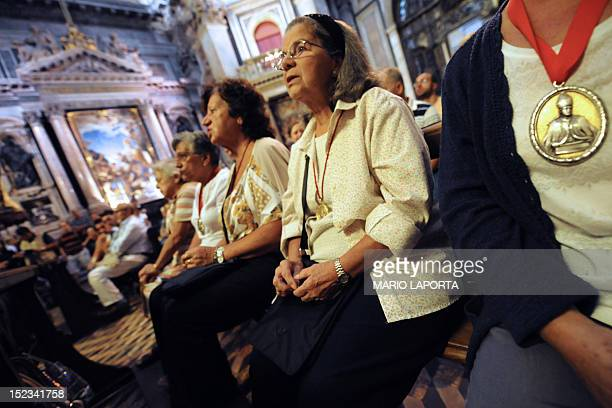 Faithful called the San Gennaro' family pray before the showing an ampoule containing blood of Saint Januarius in Naples cathedral on September 19...