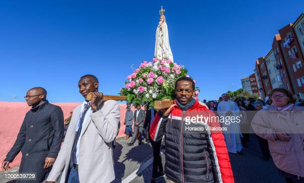 Faithful carry the figure of the Virgin of Fatima during a procession part of the Festivities of Santo Amaro a religious event based on the...