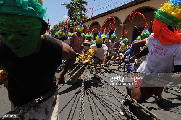 A faithful dressed as Judas is dragged with chains by the Jews during the Procession of the Chains April 9 2009 in Masatepe 45 km south of Managua...