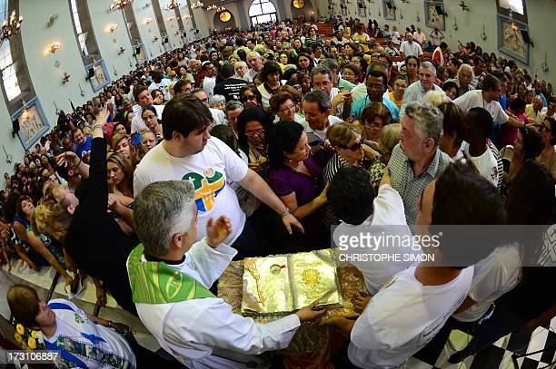 A faithful gather to touch a relic after a mass officiated by Cardinal Stanislaw Rylko to celebrate the arrival in Brazil of the relics of blessed...