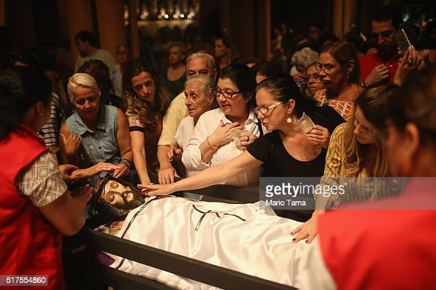 Faithful gather to touch a statue of Jesus in the Nossa Senhora da Paz church following a Good Friday procession during Semana Santa festivities on...