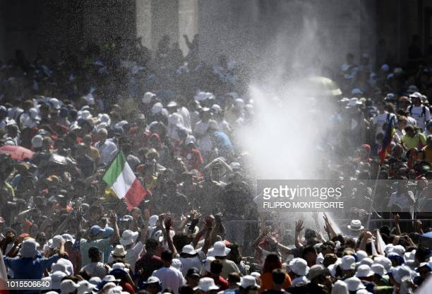 Faithful get sprayed with water as they wait for the Pope's Angelus prayer at St Peter's square in the Vatican on August 12 2018