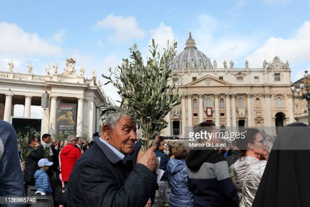 Faithful holds olive twigs during the Palm Sunday celebrations in St Peter's Square on April 14 2019 in Vatican City Climate change extreme weather...