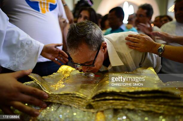 A faithful kisses a relic after a mass officiated by Cardinal Stanislaw Rylko to celebrate the arrival in Brazil of the relics of blessed John Paul...