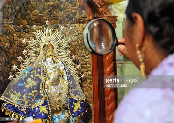 A faithful looks through a magnifying glass on April 27 at a diminutive image of the Virgen de la Letania at a sanctuary made on the Litany...