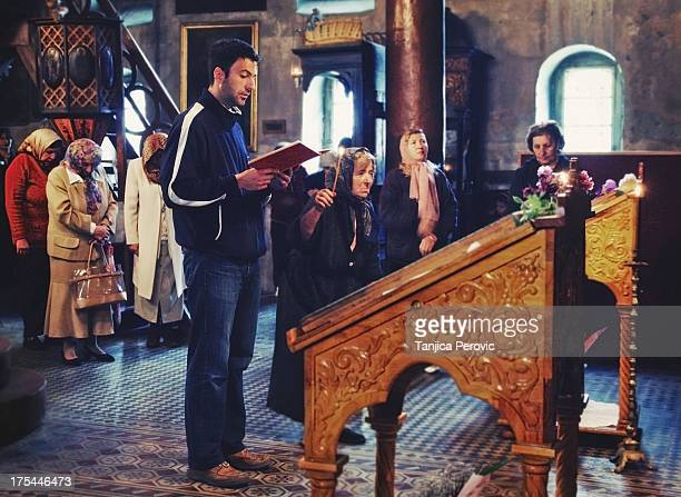 Faithful man reading the Epistle at Holy Liturgy in Orthodox Service with an old woman beside him holding a candle and some women with headdress...