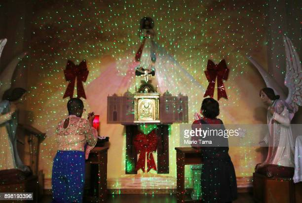 Faithful pray beneath a painting depicting Jesus Christ lit with Christmas lights during 'midnight mass' at the Nuestra Senora Del Carmen Church on...