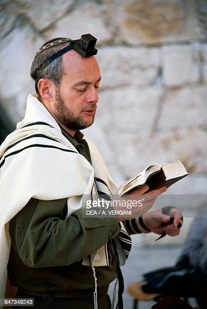 Faithful reading a prayer book in front of the Wailing Wall Jerusalem Israel