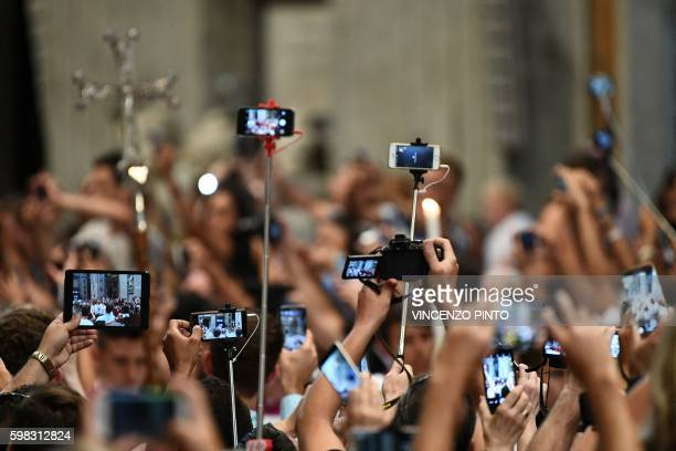 Faithful take pictures with selfie sticks and their mobile phones as Pope Francis arrives to lead a Vesper ceremony on September 1 marking the World...