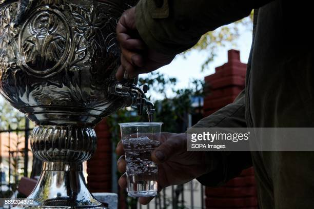 Faithful takes holy water after the litany for the Memory of Orthodox Saints Anargiroi which took place on the same day as celebration for the...