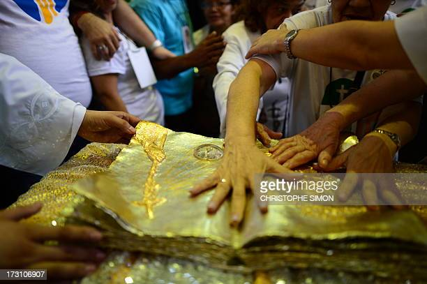 Faithful touch a relic after a mass officiated by Cardinal Stanislaw Rylko to celebrate the arrival in Brazil of the relics of blessed John Paul II...