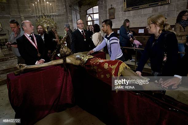 """Faithful touch an effigy of the """"Cristo de la Sangre"""" during Easter celebrations, in Palma de Mallorca on April 2, 2015. Christian believers around..."""