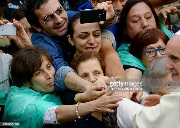 Faithful touch the hand of Pope Francis upon his arrival to Rome's Basilica di Santa Maria in Trastevere Square on June 15 2014 Pope Francis is...