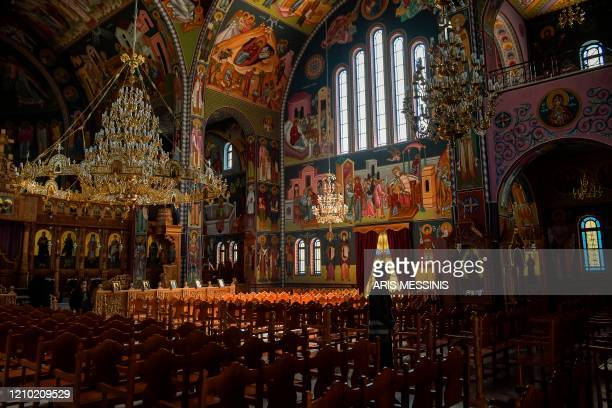 TOPSHOT Faithful walk inside an empty Orthodox church during the Holy Friday celebrations on April 17 in Athens Easter is Greece's foremost religious...