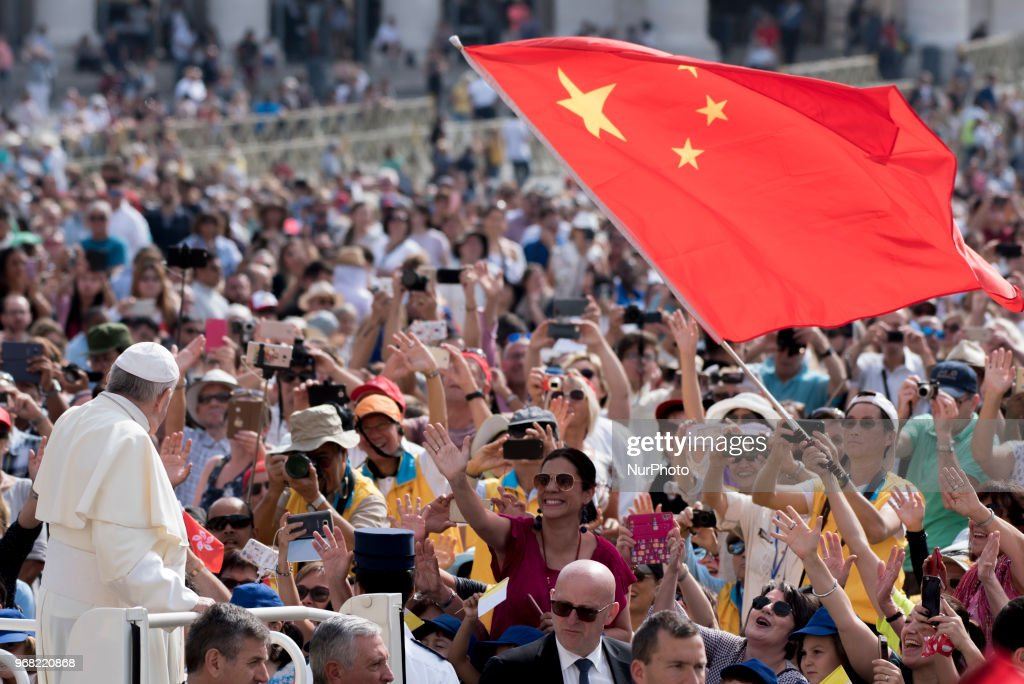A faithful waves a Chinese flag as Pope Francis arrives for his weekly general audience in St. Peter's Square at the Vatican, Wednesday, June 6, 2018.