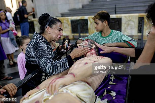 A faithful woman cries whiles she touches a sculpture of Jesus Christ during a Good Friday ceremony in front of the S�� Cathedral in Sao Paulo Brazil...