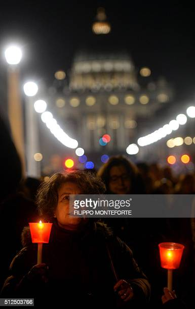 Faithfull follows the way of the cross by Jesus Christ on Via della Conciliazione leading from St.Peter's Basilica at the Vaticano in Rome on...