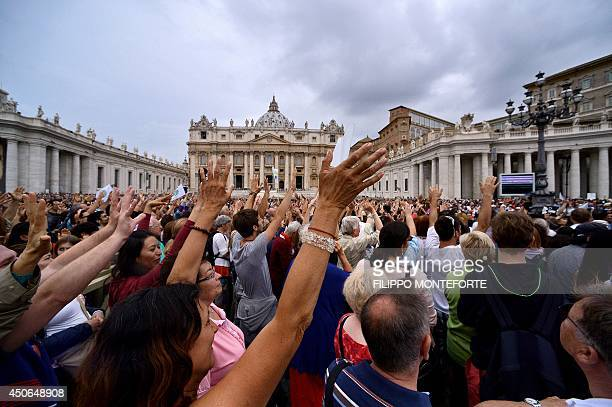 Faithfull wave their hands as they wait for Pope Francis to adresse his Sunday Angelus prayer from the window of his study overlooking StPeter's...