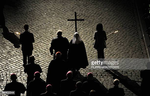 Faithfulls hold the cross in one of the stations of the Via Crucis during the Way of the Cross led by Pope Benedict XVI on Good Friday on April 10,...