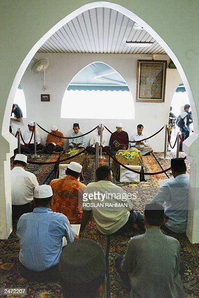Faithfuls offer prayers in front of the coffins of Iranian twins Ladan and Laleh at Ba'Alwi Mosque in Singapore 09 July 2003 The bodies of Ladan and...