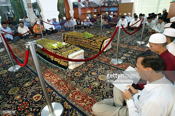 Faithfuls offer prayers in front of the coffins of Iranian twins Ladan and Laleh Bijaki at Ba'Alwi Mosque in Singapore 09 July 2003 The bodies of...